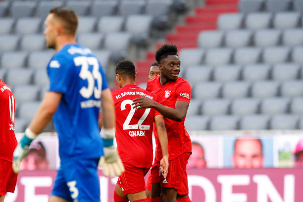 Alphonso Davies of FC Bayern Muenchen celebrates after scoring his team's fifth goal with team mate Serge Gnabry during the Bundesliga match between...