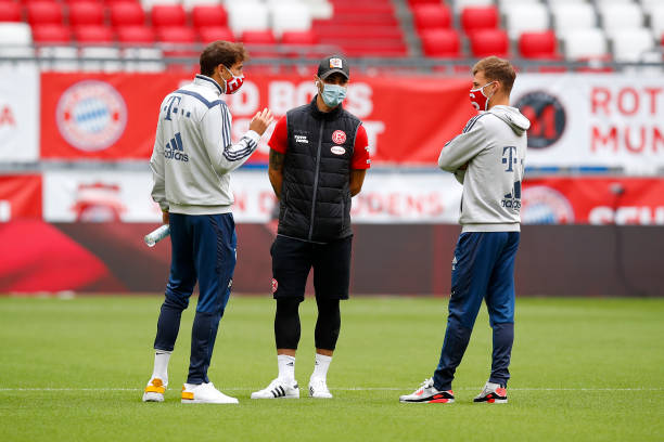 Joshua Kimmich and Leon Goretzka of FC Bayern Muenchen wear face masks as they talk to a player of Fortuna Duesseldorf prior to the Bundesliga match...